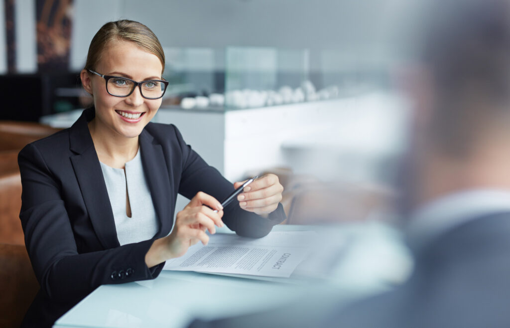 Business woman sitting at her desk and smiling at a colleague.